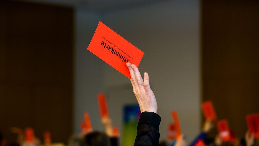 eine Hand streckt eine rote Stimmkarte nach oben, im Hintergrund viele weitere verschwommene rote Stimmkarten