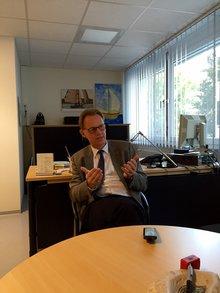 Dr. Bock sitzt im Bildzentrum am runden hellbraunen Besuchertisch seines Büros und erklärt den Verlauf einer Rehamaßnahme: auch Rentenberatung findet statt.