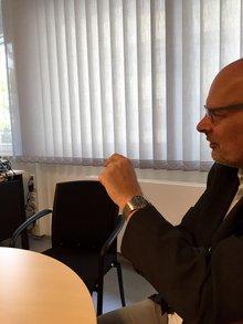 Jürgen Bothner am rechten Bildrand im Profil, Hände gestikulieren.