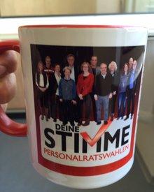 """Eine große Kaffeetasse/ein Kaffeebecher mit einem Foto der PersonalratskandidatInnen und der Bildunterschrift """" Deine Stimme - Personalratswahlen"""""""