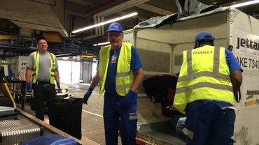 Jürgen Bothner in Arbeitskleidung steht auf und verschnauft.