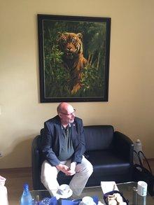 Bothner auf Ledersofa im Zoodirektorbüro unter Ölgemälde eines Tigers.
