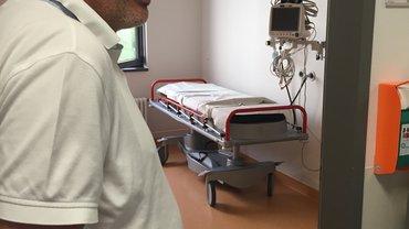 Bothner steht in der Tür zu einem Behandlungszimmer mit Liege im Hintergrund plus Monitor.
