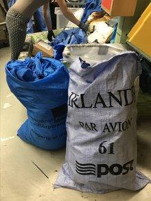 zeigt zwei gefüllte Postsäcke aus Plastik, einen grauen aus Irland und einen blauen.