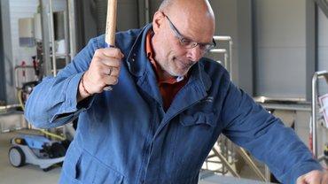 Jürgen Bothner in Blaumann vor Werkplatz schwingt einen Hammer in die Luft, guckt konzentriert.