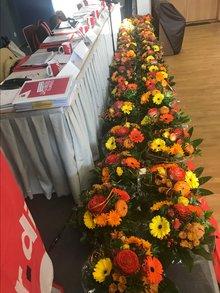 viele identische Blumensträuße auf der Bühne am Präsidiumstisch aufgereiht.