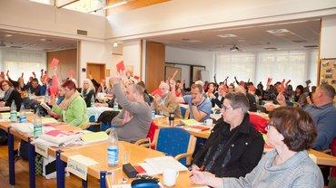 Totale: Blick auf Konferenz mit hochgereckten Händen, Stimmzettel darin.