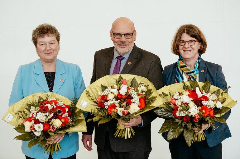 Die Landesbezirksleitung steht mit Blumenstrauß in der Hand vor weißer Wand.