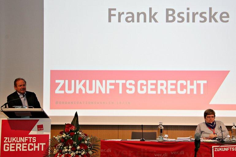 Bsirkse in der Totalen hinter Rednerpult vor Leinwand mit seinem Namen als Ankündigung