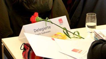 Stilleben: Ein Platz mit einer roten Nelke, Stimmkarte, Glas Wasser.