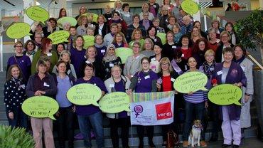 viele Frauen stehen lila angezogen auf einer breiten Treppe und halten Sprechblasenpappen mit frauenpolitischen Forderungen hoch.