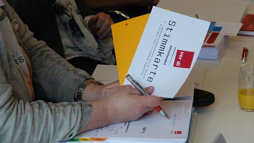 Eine Hand hält Stimmkarte, über Tisch.