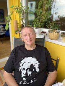 Der ehemalige langjährige Leiter des Fachbereichs Gemeinden von ver.di Hessen mit schwarzem Albert Einstein T-Shirt auf seinem Balkon in einem Gartenstuhl sitzend.