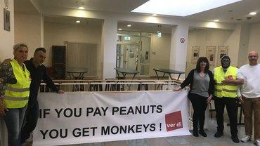 """Leute vor Transparent mit der Aufschrift """"If you pay peanuts you will get monkeys"""""""