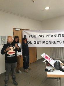 Transparent vor Eingang des Arbeitgeberberatungszimmers. Menschen mit Affenmasken davor.